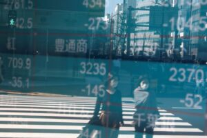 People Wearing Protective Face Masks, Following An Outbreak Of The Coronavirus, Are Reflected On A Screen Showing Nikkei Index, Outside A Brokerage In Tokyo